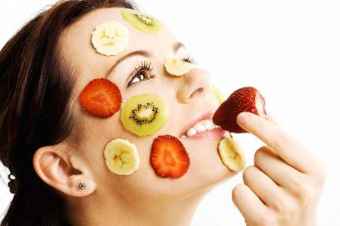woman with slices of strawberries, bananas and kiwis on her face