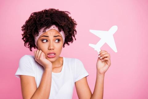 woman in white against pink background looking warily at paper airplane
